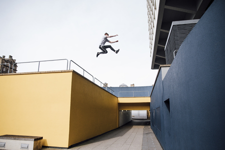 Freerunner is jumping beween colourful buildings in the city.