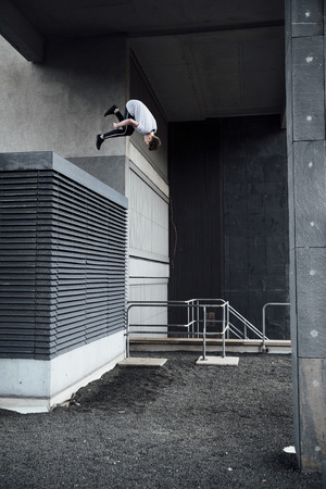 Young freerunner is doing a flip from a rooftop vent in the city.