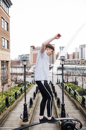 Freerunner is balancing on railings of a brdige.  版權商用圖片