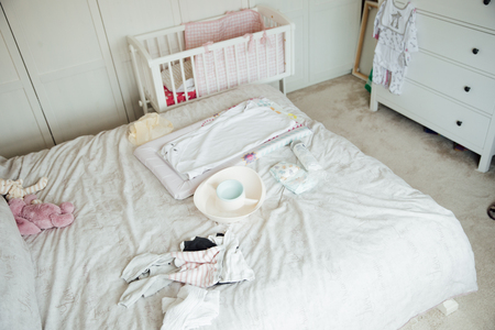 A mothers bedroom is filled with baby equipment. There is a changing mat and clothes sprawled over the bed.