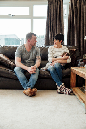 Mid adult couple are chatting on the sofa in the living room of their home while the woman is breastfeeding their baby daughter.