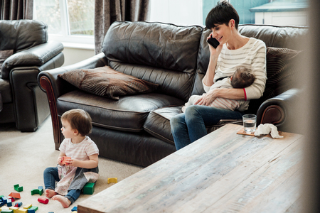 Mid adult mother is multitasking at home. she is sitting on the sofa in the living room, breast feeding her youngest baby and watching her older daughter play while talking on the phone.