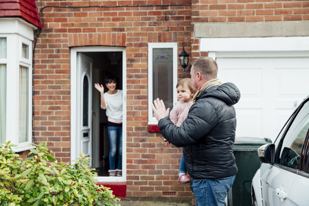 Father is carrying his baby daughter to the car and is turning round to wave at the mother who is stood at the front door of the house.