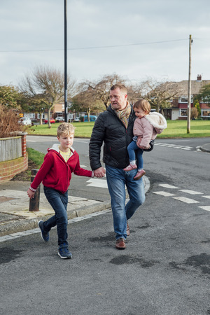 Mature man is crossing the road with his children, his son is holding his hand and he is carrying his daughter on his hip.