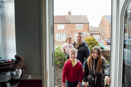 Point of view shot of a man arriving home with his three children. They are stepping through the front door of their home.