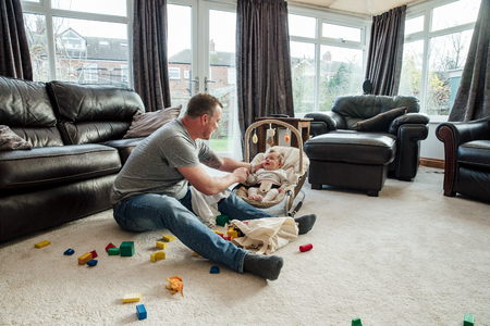 Stay at home father is relaxing in the living room with his baby daughter while she is in her baby bouncer.  Stockfoto