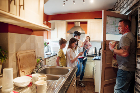A whole family are busy in the kitchen of their home. The mother is feeding the baby while the father does the dishes. The older girl is using a smartphone and her brother is watching the baby get fed.  Stock Photo