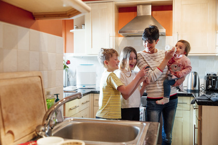 Girl and her brother are showing their mum something on their smartphone. They are all laughing and the mother has the baby on her hip, feeding her at the same time.  Stock Photo