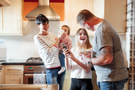 A family are socialising in the kitchen. the mother is feeding the baby a bottle and the little girl is showing her dad something funny on her smart phone.