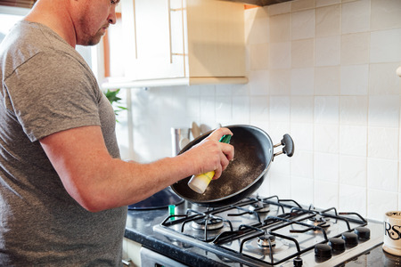 Close up shot of a mature man spraying some frying oil onto a cooking wok in the kitchen of his home.