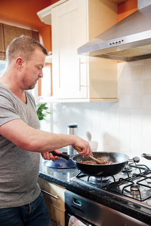 Mature man is making a spagetti bolognese at home. He is browning off the mince in a wok with onions. Imagens