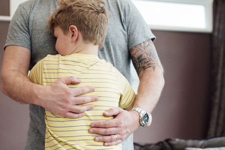 Little boy is cuddling his father at home. He has his arms round his fathers torso and the father is holding his son close to him.