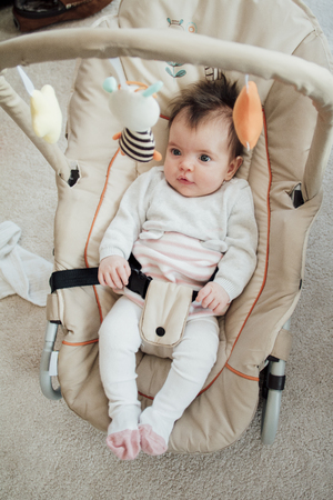 Portrait of a baby girl in her bouncer chair at home.