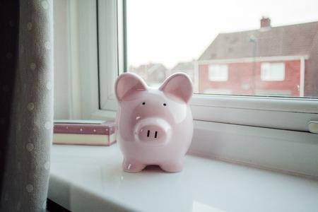Piggybank stands on a windowsill in a home.