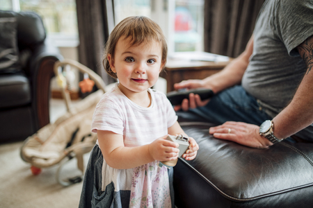 Little girl has stopped playing with her father at home to look at the camera. She is holding a toy.
