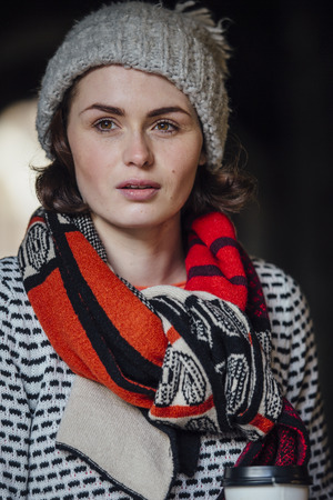 Winter portrait of a woman holding a coffee cup wearing a scarf and hat.
