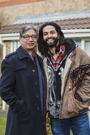 portrait of a happy father and his son on the driveway of their home. Imagens