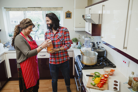 Mid adult man is helping his mother to make a curry in the kitchen of their home. They are opening a tub of ground ginger.  Stock Photo