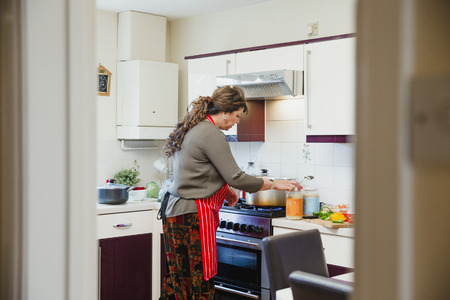 Mature woman is standing at the cooker in the kitchen of her home, preparing ingredients for a curry.  Stock Photo