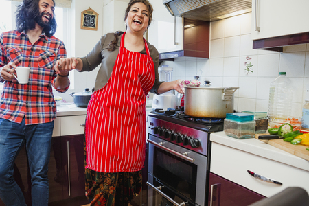 Mature woman is having fun making a curry at home with company from her mid adult son.  Stock Photo