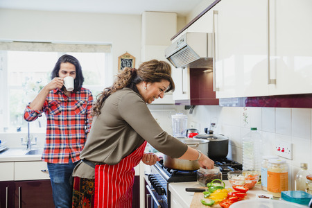 Mid adult man is relaxing in the kitchen talking to his mother while she prepares a curry on the cooker.