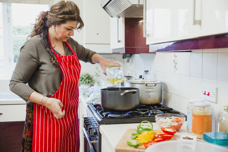 Mature woman is cooking a curry in the kitchen of her home. She is adding oil to a pan.