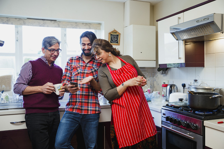 Mid adult man is showing his parents something on his smartphone while they are in the kitchen of their home.