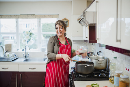 Mature woman is talking and laughing with someone out of the frame while she makes dinner at the cooker.