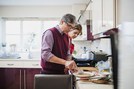 Mature couple are preparing a Pakistani meal at home. The man is cutting chapati and the woman is watching him closely.