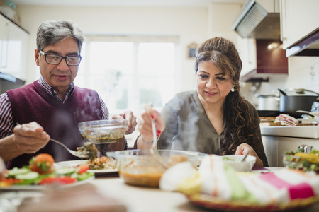 Mature couple are enjoying a homemade curry with salad at home.