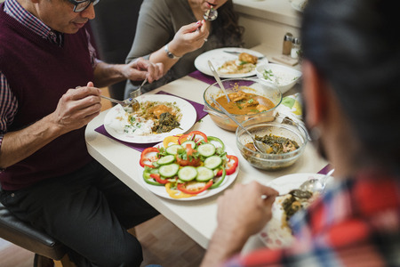 Close up shot of homemade indian food on a family dining table. They are eating curry with salad.