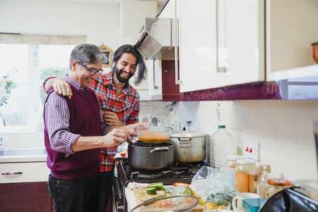 Mid adult man is looking over his father's shoulder as he prepares a curry at home.  Stock Photo