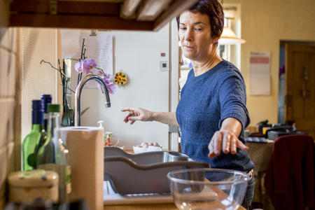 Woman reaches towards a glass bowl as she prepares dinner for Thanksgiving.