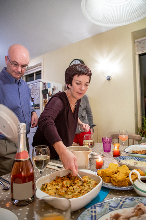 Woman serves food to her family for Thanksgiving.