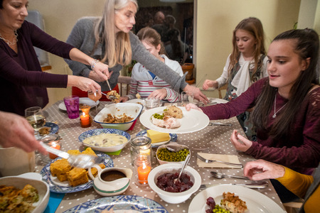 A family help themselves to a meal at Thanksgiving. Stock Photo