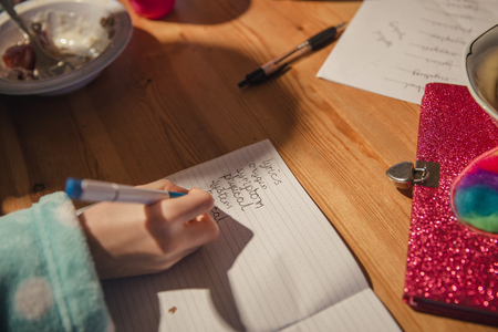 Close-up of a little girls hand writing her spellings out. Doing homework before school.