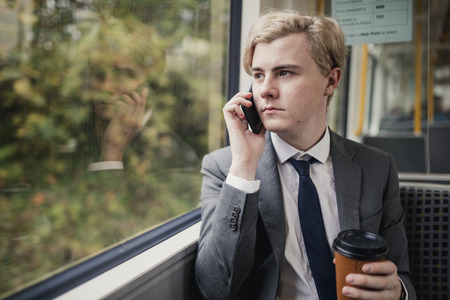 Businessman on the phone with a cup of coffee on the train during his commute to work.
