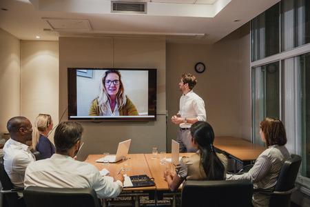Grupo de gente de negocios que tiene una reunión de videoconferencia nocturna. Sentarse alrededor de una mesa de conferencias para hablar y establecer contactos.