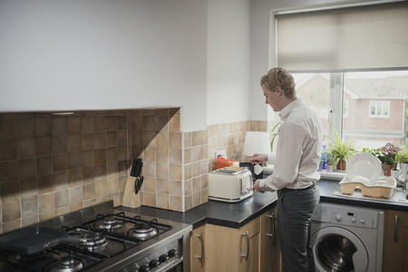 Wide angle, rear view of a young adult businessman making some toast for breakfast before work.  Foto de archivo