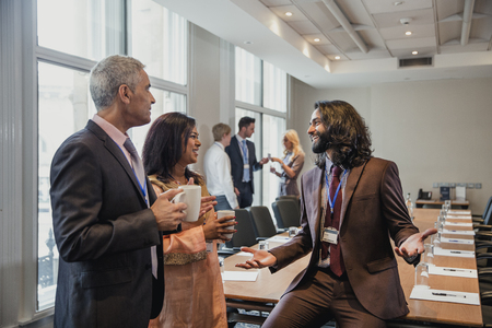 Small group of business men and women talking before a conference.  Stock Photo
