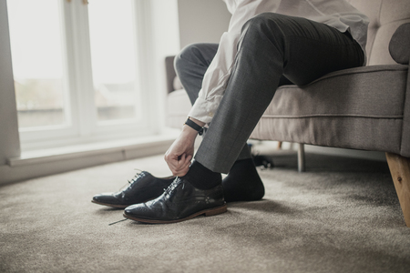 Unrecognisable person adult male sitting on a sofa in a domestic room tying his shoelaces. Stock Photo