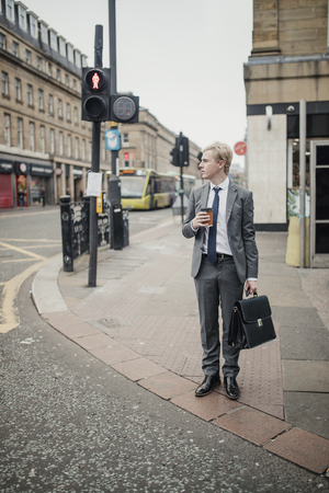 Front view of a young businessman waiting at the traffic lights to cross the road. Archivio Fotografico - 103100273