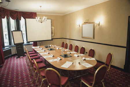 Wide angle interior layout of an empty board room with a flip chart and a projector screen set up.