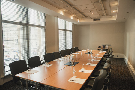 Wide angle interior shot of a business board room empty and set up for a meeting.