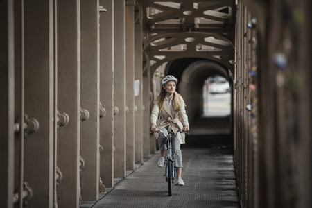 Wide angle, front view of a young female adult cycling over a bridge on the way to work. 스톡 콘텐츠