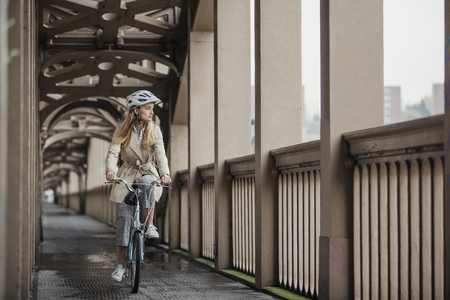 Front view of a businesswoman cycling over a bridge to get to her meeting.