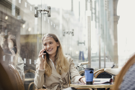 Front View of a young adult businesswoman making a phone call and having a coffee before work. Stok Fotoğraf