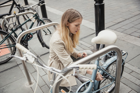 Young businesswoman locking up her bicycle at the rack before she goes into work.