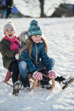 Two little girls are having fun on a sled in the snow.