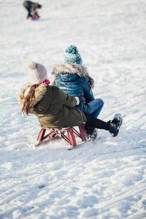Rear view of two girls sledding down a hill together in the snow.
